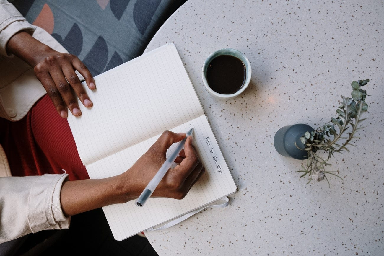person holding white pen and white paper