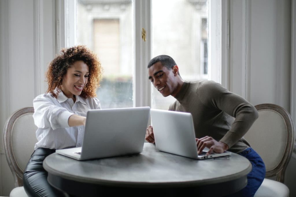 positive young ethnic colleagues using laptop on round table near window at home