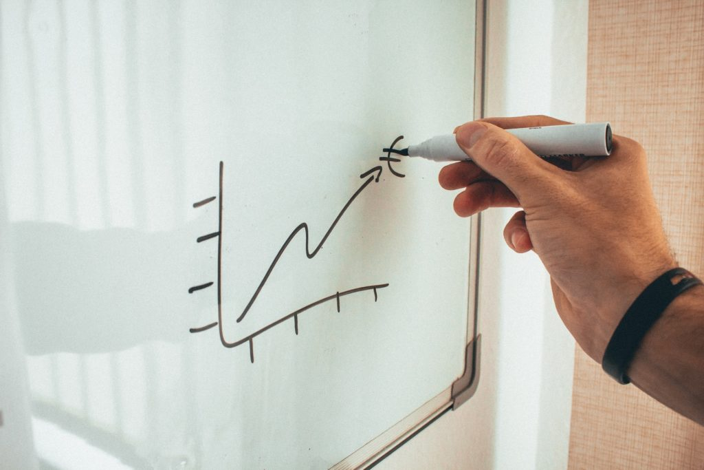 Man drawing on whiteboard to illustrate benefits of remarketing and retargeting